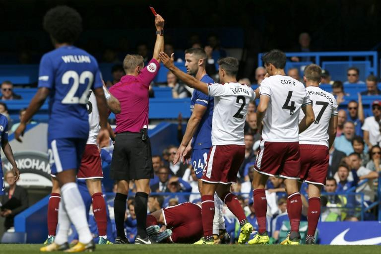 Chelsea's Gary Cahill (C) is shown a red card by referee Craig Pawson after a foul on Burnley's Steven Defour during their English Premier League match, at Stamford Bridge in London, on August 12, 2017