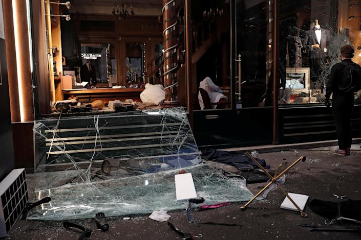 """A man stops in front of a vandalized tailor's shop during a demonstration by the """"yellow vests"""" movement in Paris, France, Dec. 8, 2018. (Photo: Benoit Tessier/Reuters)"""