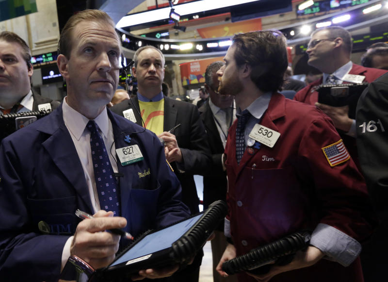 """Michael Smyth, left, works with fellow traders on the floor of the New York Stock Exchange, Wednesday, March 26, 2014. The stock market opened higher Wednesday after a strong report on American manufacturing. The maker of the hit game """"Candy Crush Saga"""" flopped in its market debut.(AP Photo/Richard Drew)"""