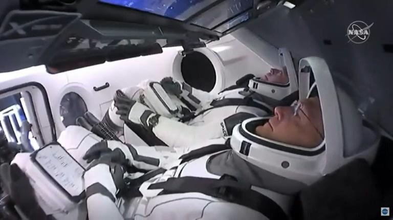 NASA astronauts Bob Behnken (rear) and Doug Hurley are strapped in the SpaceX Crew Dragon capsule