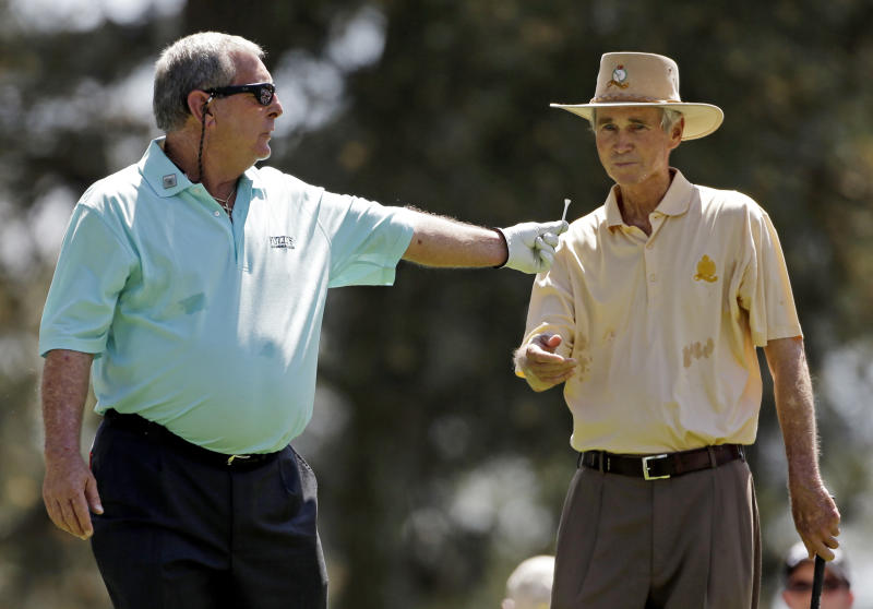 Fuzzy Zoeller hands a tee to Hubert Green after teeing off on the first hole during the par three competition before the Masters golf tournament Wednesday, April 10, 2013, in Augusta, Ga. (AP Photo/Darron Cummings)