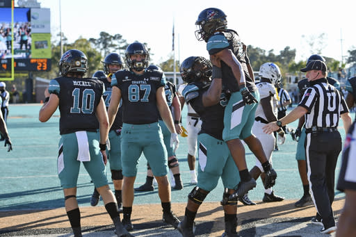 Coastal Carolina's Reese White is lifted by teammate Willie Lampkin, right, after scoring the go-ahead touchdown in the second half of an NCAA college football game against Appalachian State, Saturday, Nov. 21, 2020, in Conway, S.C. Coastal Carolina won 34-23. (AP Photo/Richard Shiro)