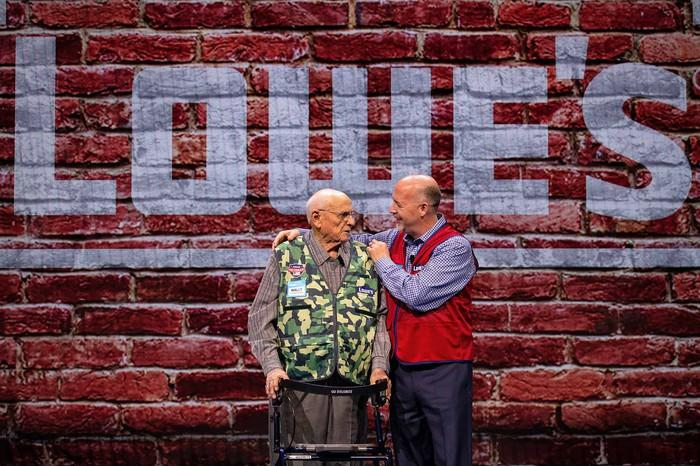 Lowe's executive embraces a veteran in a camouflage vest during a Lowe's presentation.