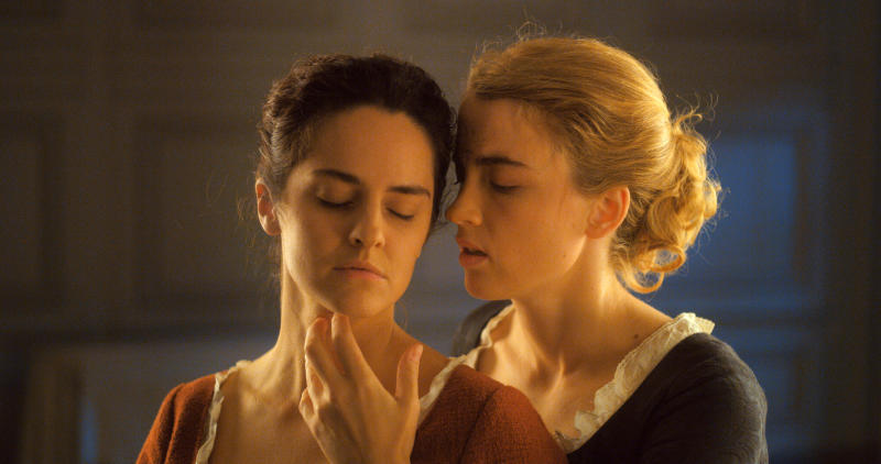 """This image released by Neon shows Noémie Merlant, left, and Adèle Haenel in a scene from """"Portrait of a Lady on Fire."""" (Neon via AP)"""