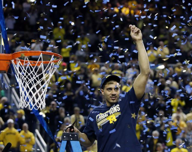 ANN ARBOR, MI - MARCH 8: Jordan Morgan #52 of the Michigan Wolverines holds up his piece of the net following a 84-80 win over the Indiana Hoosiers during the second half of a basketball game on March 8, 2014, in Ann Arbor, Michigan. (Photo by Duane Burleson/Getty Images)
