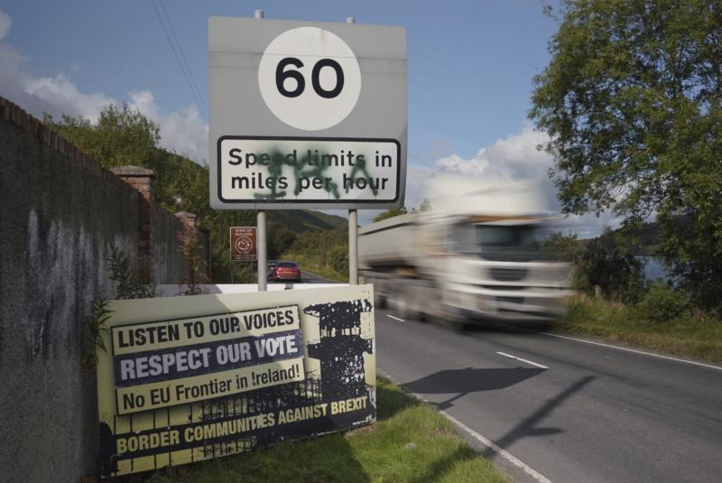 A truck races past a sign against the reestablishment of a hard border between Northern Ireland and the Republic of Ireland on Friday, Sep. 27, 2019. People in Ireland are reacting with dismay and disbelief at the latest reports of Britain's proposed alternative to the Irish backstop, with preliminary papers suggesting the UK government will propose customs a few miles away from the border. (AP Photo/David Keyton)