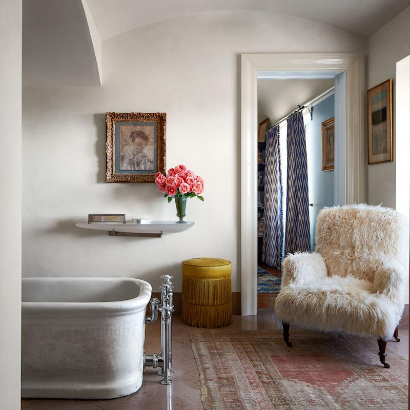 The master bath features a goatskin-covered armchair. Vintage rug.
