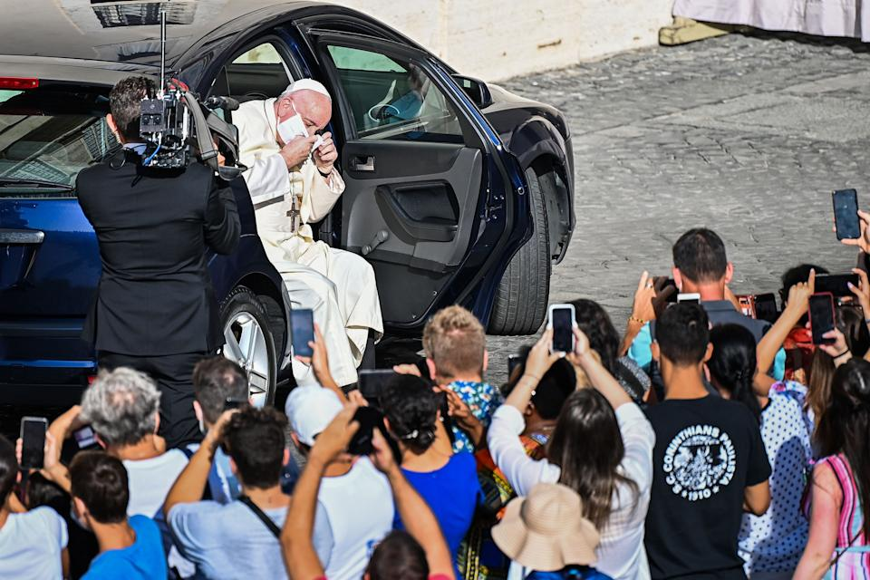 Pope Francis takes off his face mask as he arrives by car to hold a limited public audience at the San Damaso courtyard in The Vatican on September 9, 2020, during the COVID-19 infection, caused by the novel coronavirus.