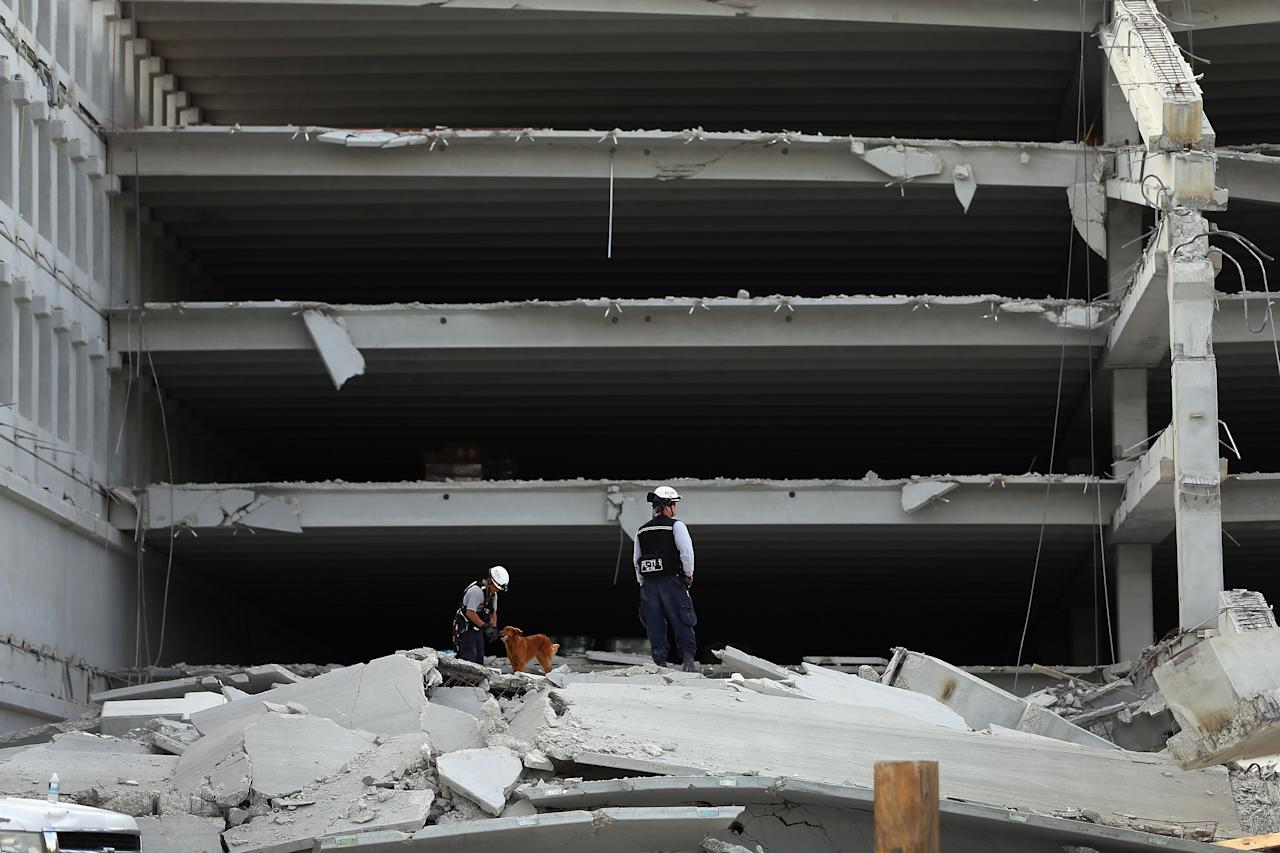 DORAL, FL - OCTOBER 10:  Miami-Dade Fire Rescue search and rescue workers search in the rubble of a four-story parking garage that was under construction and collapsed at the Miami Dade College's West Campus on October 10, 2012 in Doral, Florida.  Early reports indicate one person was killed in the collapse at least seven people injured and one is still trapped.  (Photo by Joe Raedle/Getty Images)