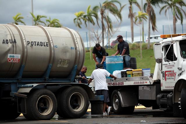 Local residents fill cans of water in Carolina, Puerto Rico, on Saturday.