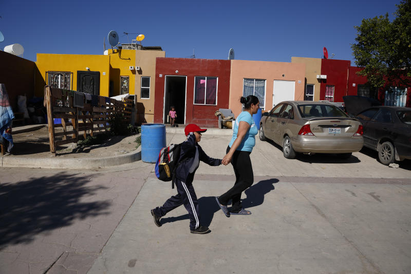 In this Jan. 28, 2020, photo, Ruth Aracely Monroy, right, rushes her son, Nahum Perla, left, to school from their home on the outskirts of Tijuana, Mexico. They were among the first sent back to Mexico under a Trump administration policy that dramatically reshaped the scene at the U.S.-Mexico border by returning migrants to Mexico to wait out their U.S. asylum process. (AP Photo/Gregory Bull)