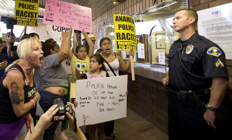 Activist Marlena Carrillo shouts at police inside the Anaheim Police Department Sunday July 22, 2012 where a press conference took place in response to the officer involved killing of Manuel Diaz Saturday. Demonstrators stormed a police department in Orange County, Calif., on Sunday to protest an officer-involved shooting that left an unarmed man dead. (AP Photo/The Orange County Register, Mindy Schauer) MAGS OUT; LOS ANGELES TIMES OUT MANDATORY CREDIT, MINDY SCHAUER, THE ORANGE COUNTY REGISTER.