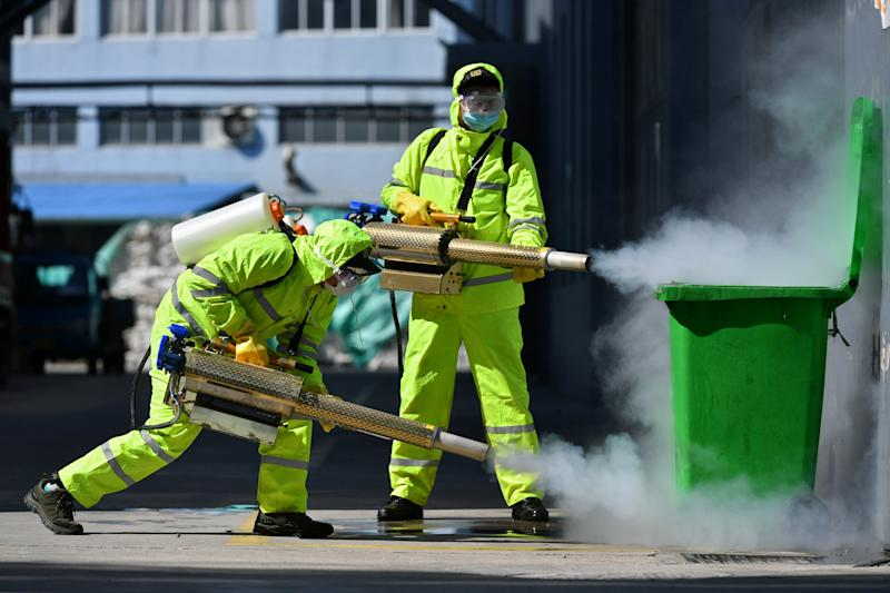 Volunteers in protective suits disinfect a factory with sanitizing equipment, as the country is hit by an outbreak of the novel coronavirus, in Huzhou, Zhejiang province, China February 18, 2020. China Daily via REUTERS