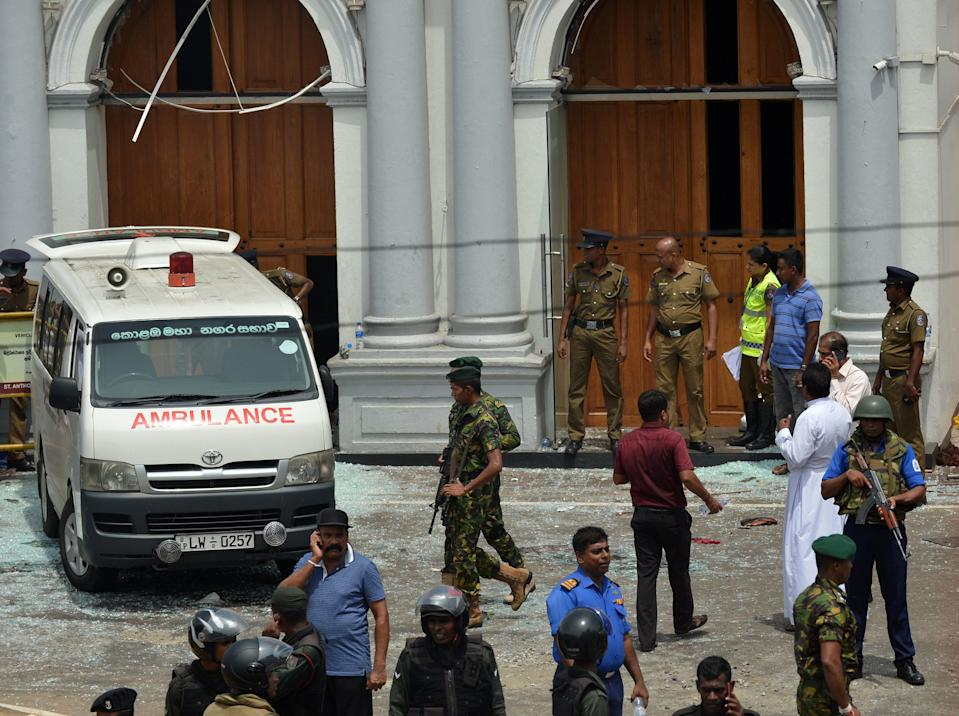 An ambulance is seen outside the church premises with gathered people and security personnel following a blast at the St Anthony's Shrine. Source: Getty Images