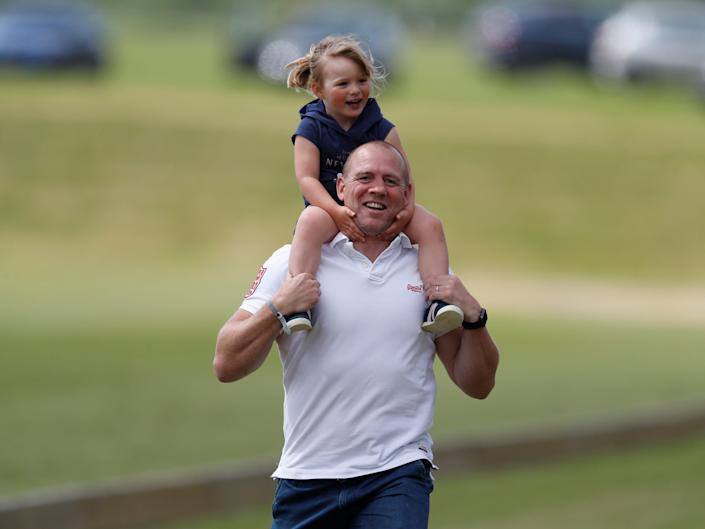 Mia Tindall rides on her father Mike Tindall's shoulders.