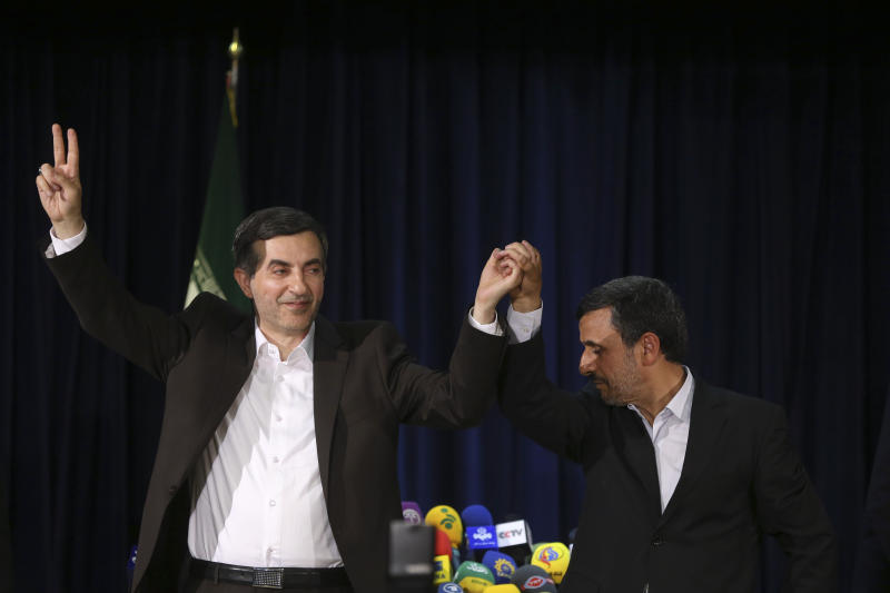 In this picture taken on Saturday, May 11, 2013, Iranian President Mahmoud Ahmadinejad, right, joins hands with his close ally Esfandiar Rahim Mashaei, as he flashes a victory sign, at the start of their press conference, after registering the candidacy of Mashaei for the upcoming presidential election, at the election headquarters of the interior ministry, in Tehran, Iran.  By now, President Mahmoud Ahmadinejad is well accustomed to enduring blows from Iran's ruling clerics as his reputation fell from favored son to political outcast. But their intended parting shot _ barring his chief aide from the presidential race _ may be just the opening act in Ahmadinejad's reinvention as a self-styled opposition force. (AP Photo/Ebrahim Noroozi)