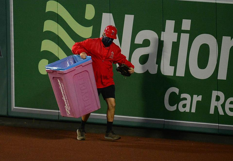 A stadium worker removes a trash can that was thrown onto the field at Angel Stadium.