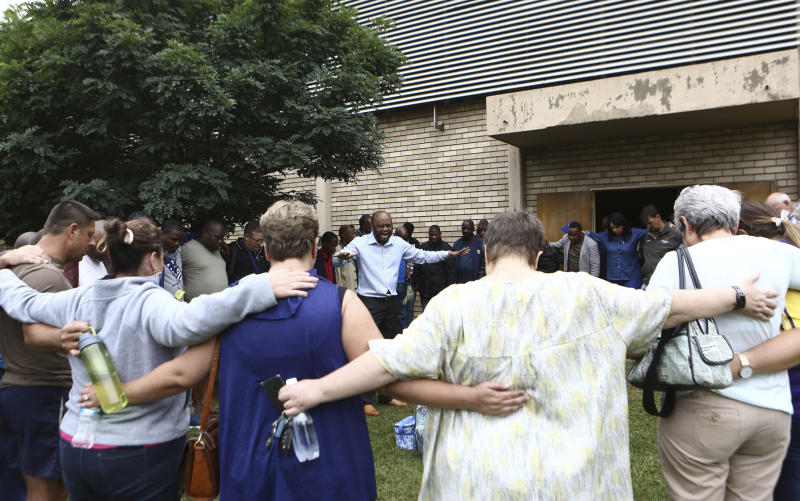 A pastor leads people in prayer at the site of a walkway collapse at the Driehoek High School in Vanderbijlpark, South Africa, Friday, Feb. 1, 2019. At least 3 students were killed and scores injured at the school near Johannesburg, a South African official said. (AP Photo)