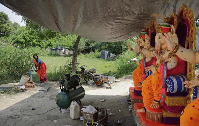 <p>A member of an artisan family that makes idols fetches water from a hand pump as idols of Hindu god Ganesha are kept for sale at a workshop in New Delhi, India, Wednesday, September 12, 2018. The idols are being prepared ahead of the 'Ganesh Chaturthi' festival that celebrates the birthday of the elephant headed god. (AP Photo/Altaf Qadri) </p>