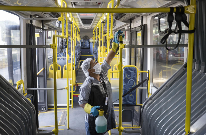 An employee disinfects a bus in a bus terminal during a quarantine imposed by the state government to help contain the spread of the new coronavirus in Sao Paulo, Brazil, Monday, May 4, 2020. (AP Photo/Andre Penner)