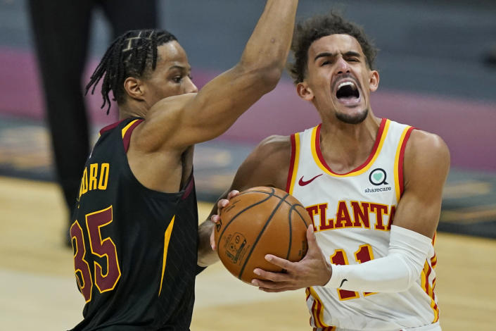 Atlanta Hawks' Trae Young (11) drives to the basket against Cleveland Cavaliers' Isaac Okoro (35) in the second half of an NBA basketball game, Tuesday, Feb. 23, 2021, in Cleveland. The Cavaliers won 112-111. (AP Photo/Tony Dejak)
