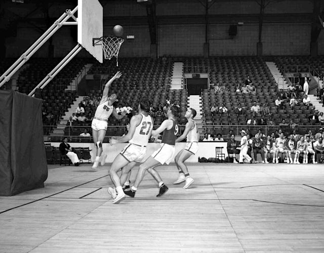 Captain of the United States basketball team J.B.Renick, number 55, left jumping, scores in the Olympic Games match against Switzerland, at Harringay Arena, London, July 30, 1948. From left to right; Renick; Wallace C. Jones, USA; Marc Bossy, Switzerland; unidentified player. America won the match by 86 points to 21. (AP Photo)