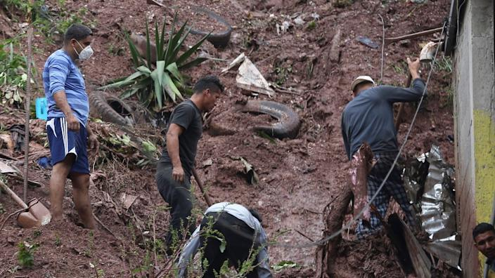 A group of people work to recover belongings from the debris of their homes following a landslide caused by the rains of tropical storm Eta in the city of Tegucigalpa, Honduras, 05 November 2020