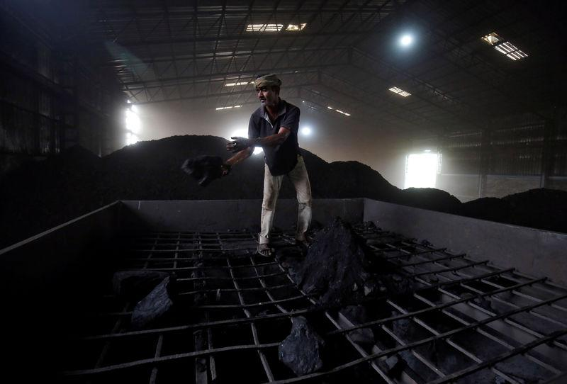A worker shovels coal in a supply truck at a yard on the outskirts of Ahmedabad