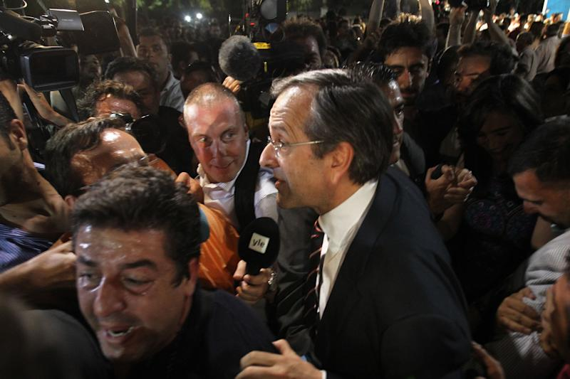 Leader of the New Democracy conservative party Antonis Samaras surrounded by media, leaves an elections kiosk after speaking to his supporters at Syntagma square in Athens, late Sunday, June 17, 2012. The pro-bailout New Democracy party came in first Sunday in Greece's national election, and its leader has proposed forming a pro-euro coalition government. (AP Photo/Petros Karadjias)