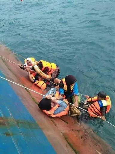 Waves swamped the boat's deck, taking trucks and other vehicles into the sea, as rescuers battled high winds and rough seas to pluck victims from the water