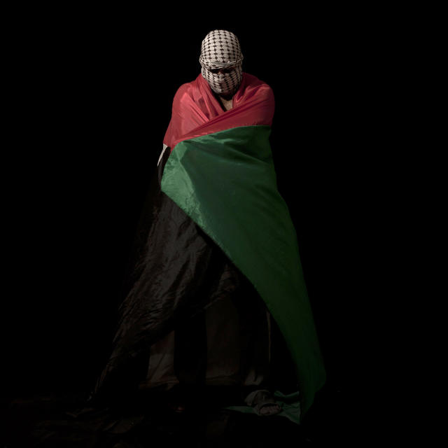 <p>A Palestinian stone thrower — wrapped in a Palestinian flag and masked in a kaffiyeh to conceal his identity — poses for a portrait in the West Bank village of Bilin, near Ramallah on June 13, 2012. (Photo: Oded Balilty/AP) </p>