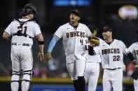 Arizona Diamondbacks' Stephen Vogt, left, celebrates a win against the Milwaukee Brewers with Diamondbacks' Ketel Marte (4) and Josh Reddick (22) after the final out of the ninth inning of a baseball game Monday, June 21, 2021, in Phoenix. The Diamondbacks defeated the Brewers 5-1. (AP Photo/Ross D. Franklin)