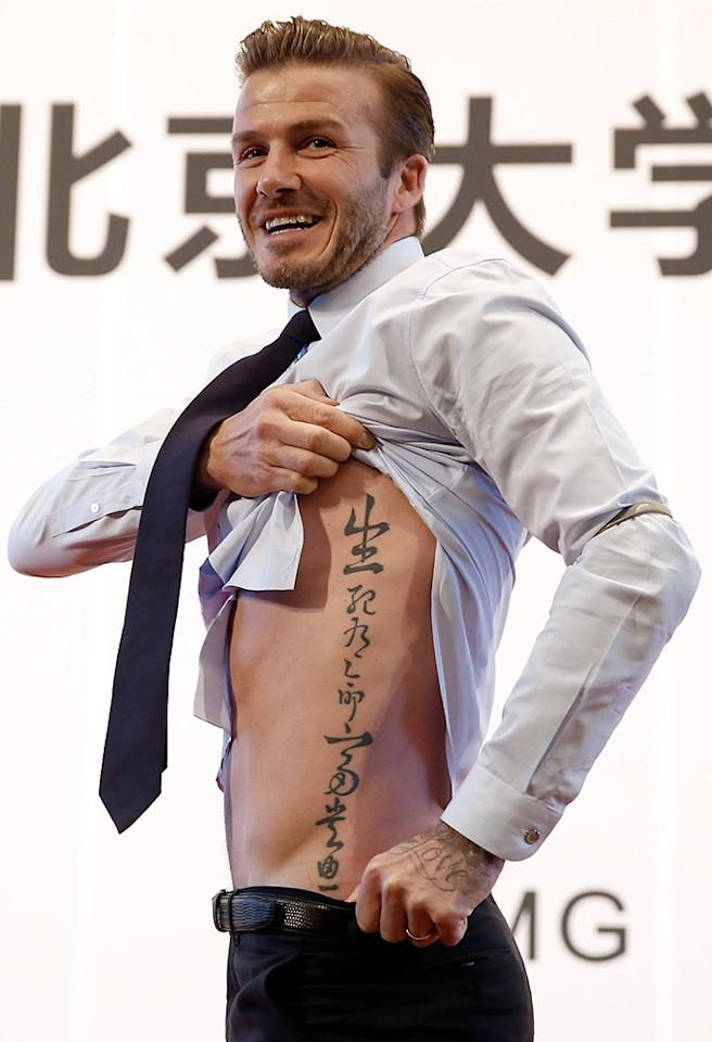 Who cares who designed David Beckham's shirt and tie? His new tattoo (and those abs!) are 2 Hot 2 Handle. (3/24/2013)