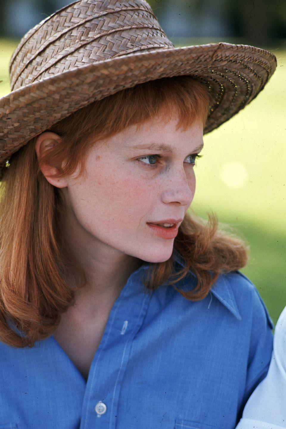 <p>Farrow wears a light blue button-down and straw hat on vacation in Bermuda in 1969, where she changed up her hair again with a long red look. </p>