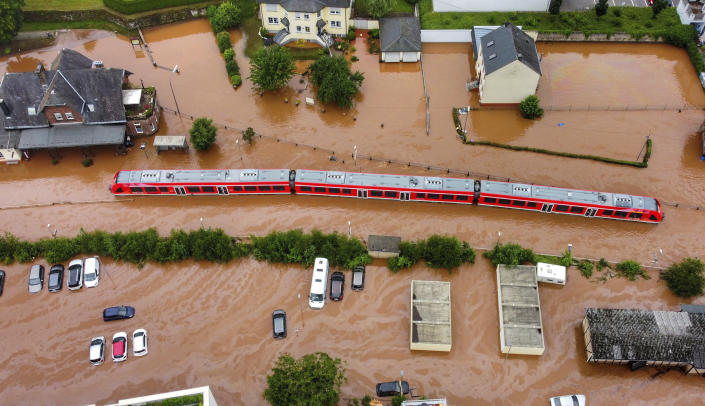 A regional train sits in the flood waters at the local station in Kordel, Germany, Thursday July 15, 2021 after it was flooded by the high waters of the Kyll river. (Sebastian Schmitt/dpa via AP)