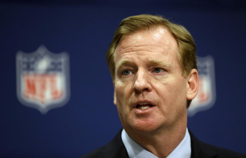 A tight shot of Roger Goodell's face in front of the NFL logo.