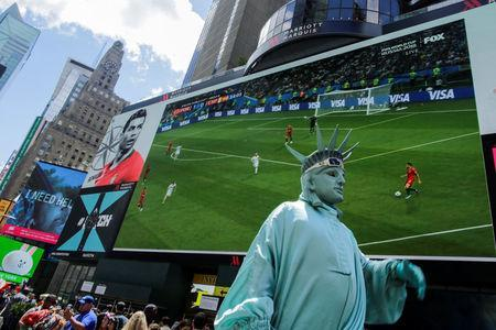 People watch the World Cup Group B - Portugal vs Spain soccer match at Times Square in New York City, New York, U.S., June 15, 2018. REUTERS/Eduardo Munoz