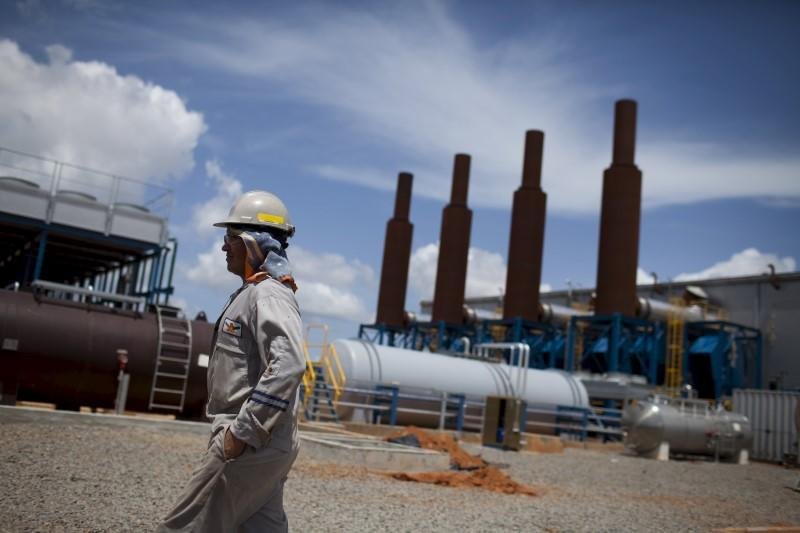 File photo of an oil worker walking past an oil installation operated by Venezuela's state oil company PDVSA in Morichal