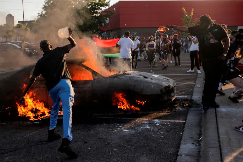 FILE PHOTO: People react as a car burns at the parking lot of a Target store during protests in Minneapolis