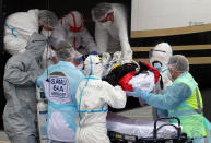 FILE- In this March 19, 2021, file photo, a patient from the Paris region and affected by the COVID-19 virus is taken out a plane at the Biarritz's airport, southwestern France. France's president say he has nothing to be sorry about for refusing to impose a third virus lockdown earlier this year, even though his country is now facing surging infections that are straining hospitals and more than 1,000 people with the virus are dying every week. (AP Photo/Bob Edme, File)