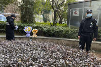 "A security guard stands neaby as a man visiting the Wuhan Central Hospital leaves flowers in memory of Li Wenliang, the whistleblower doctor who sounded the alarm and was reprimanded by local police for it in the early days of Wuhan's pandemic, prior to the anniversary of his death, in central China's Hubei province, Saturday, Feb. 6, 2021. Dr. Li Wenliang died in the early hours of Feb. 7 from the virus first detected in this Chinese city. A small stream of people marked the anniversary at the hospital. The 34-year-old became a beloved figure and a potent symbol in China after it was revealed that he was one the whistleblowers who authorities had punished early for ""spreading rumors"" about a SARS-like virus. (AP Photo/Ng Han Guan)"