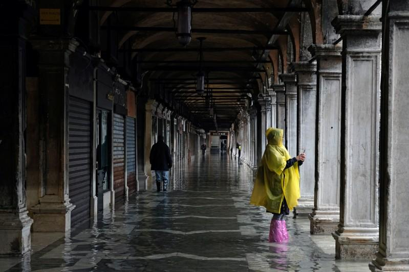 Tourists walk in St. Mark's Square after days of severe flooding in Venice