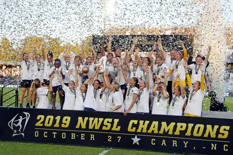 FILE - The North Carolina Courage celebrate with the championship trophy following their win over the Chicago Red Stars in an NWSL championship soccer game in Cary, N.C., in this Sunday, Oct. 27, 2019, file photo. The National Women's Soccer League will not play the games scheduled for this weekend as it deals with the fallout from allegations of sexual misconduct against a former coach. North Carolina Courage coach Paul Riley was fired by the team following a report in The Athletic that detailed the alleged misconduct, which included claims from two former players of sexual coercion. The NWSL did not specify Friday, Oct. 1, 2021, whether the games were canceled or postponed. (AP Photo/Karl B DeBlaker, File)