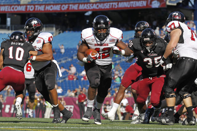 Northern Illinois running back Cameron Stingily (42) scores a touchdown as fullback Rob Sterling (47) and offensive linesman Jared Volk (77) block on the play against Massachusetts defensive back Devin Brown (10) and defensive lineman Stanley Andre (35) during the first half of an NCAA football game in Foxborough, Mass., Saturday, Nov. 2, 2013. (AP Photo/Stew Milne)