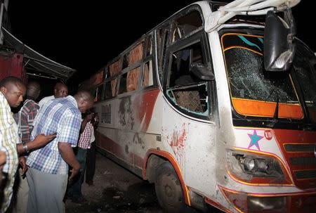 Plain-clothed policemen check the damage on a passenger bus at the scene of an explosion at the populous Mwembe Tayari market