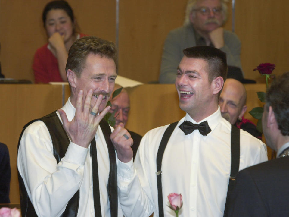 Frank Wittebrood, left, and Peter Wittebrood-Lemke, show their tattooed rings to Amsterdam mayor Job Cohen, right, after exchanging vows at Amsterdam's City Hall early Sunday, April 1, 2001. The pair was among four couples to get married under a new law which took effect April 1 and is the world's first such law allowing same-sex marriages with equal rights. (AP Photo/Peter Dejong)