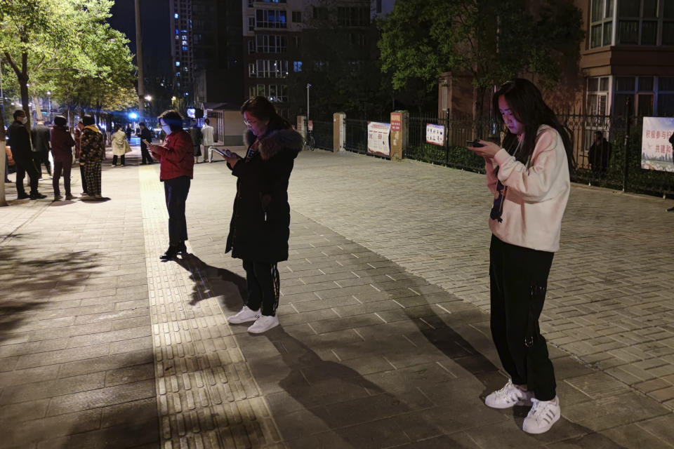 In this photo released by China's Xinhua News Agency, people stand on a street after an earthquake in Xining in northwestern China's Qinghai Province, early Saturday, May 22, 2021. A pair of strong earthquakes struck two provinces in China overnight on Saturday. (Zhang Long/Xinhua via AP)