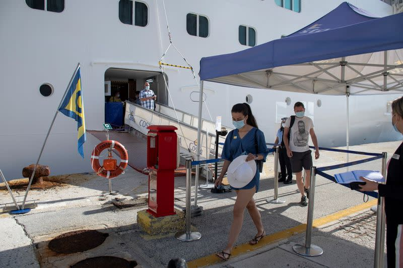 Passengers wearing protective face mask disembark from the Costa Luminosa cruise ship at the port of the island of Corfu