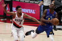 Portland Trail Blazers guard CJ McCollum, left, fouls Denver Nuggets forward Will Barton during the first half of an NBA basketball game in Portland, Ore., Wednesday, April 21, 2021. (AP Photo/Steve Dykes)