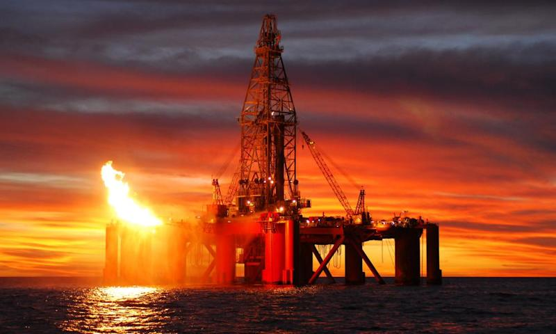 Silhouette of ocean oil rig at sunse